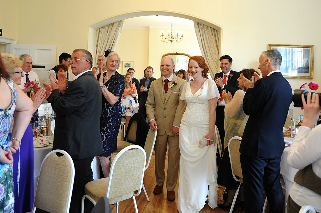 Beaming newlyweds walk into the Russell Suite at Surrey venue Pembroke Lodge past clapping and cheering guests to start their wedding breakfast