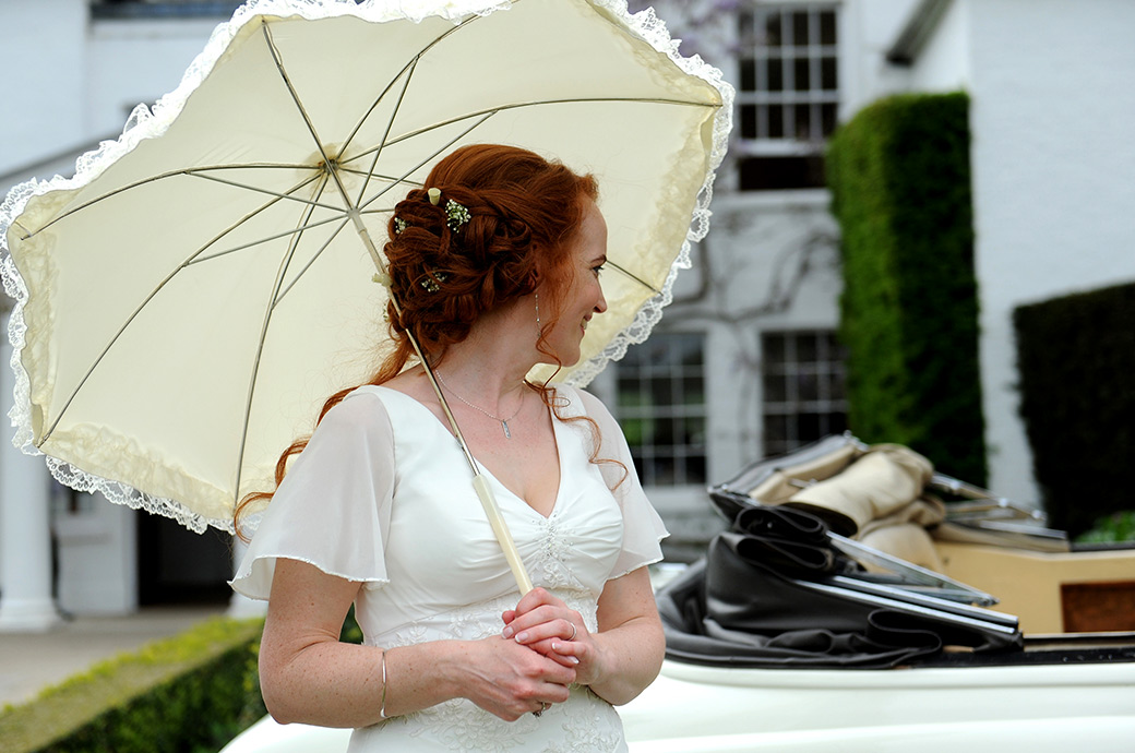 Bride smiles with her head turned and cream parasol in hand to her Groom sitting in a white vintage Bentley convertible in front of Surrey wedding venue Pembroke Lodge