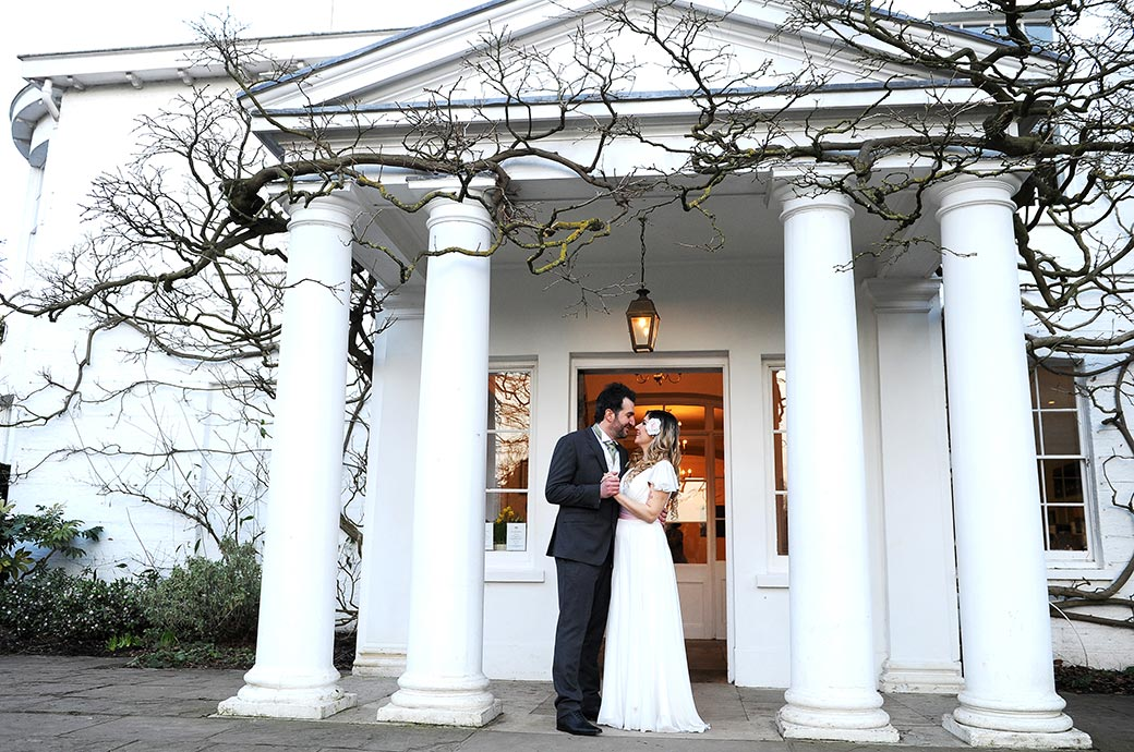 Treasured moment captured of a Bride and groom in the pillared front entrance to the popular wedding venue Pembroke Lodge in Richmond Park