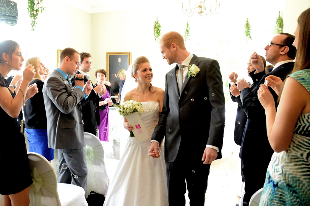 The newly-weds walk smiling down the aisle as guests blow bubbles in the bright wedding photo taken in The Russell Suite at  Pembroke Lodge in Surrey