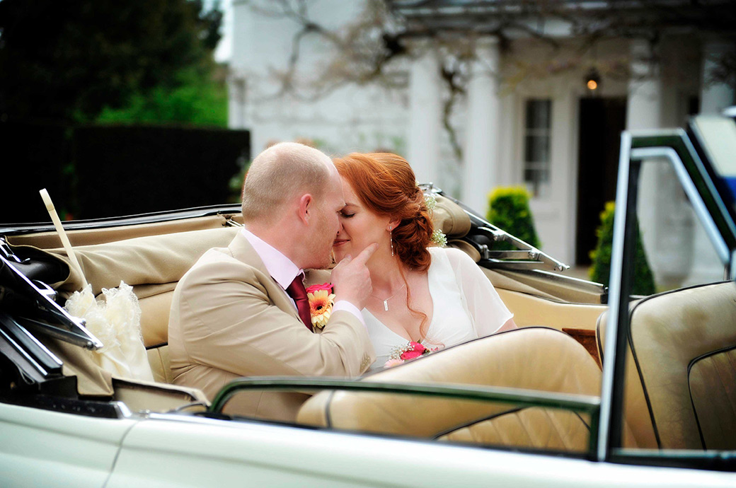 A romantic intimate moment for young lovers at Surrey wedding venue Pembroke Lodge in Richmond Park as they sit in the back of their white vintage convertible Bentley