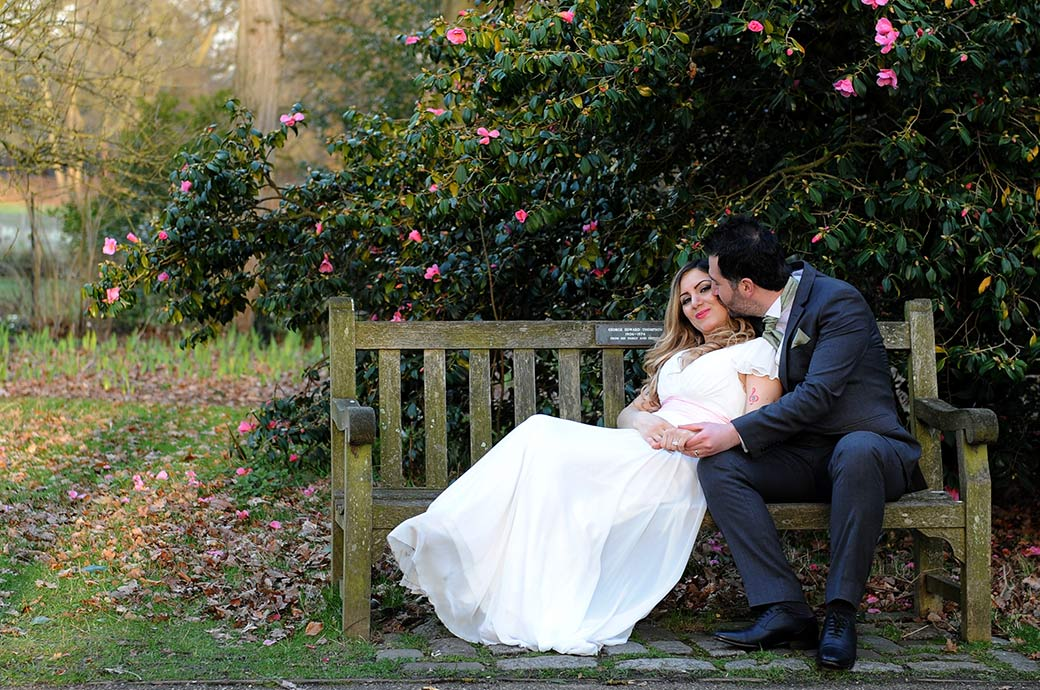 Groom holds his Bride's hands as he kisses her on a park bench in Richmond Park in this wedding photo taken at Pembroke Lodge Surrey