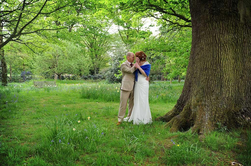 Passionate intimate moments as a Bride and Groom hold each other by the oak trees in Richmond Park Surrey after their marriage at the Pembroke Lodge wedding venue