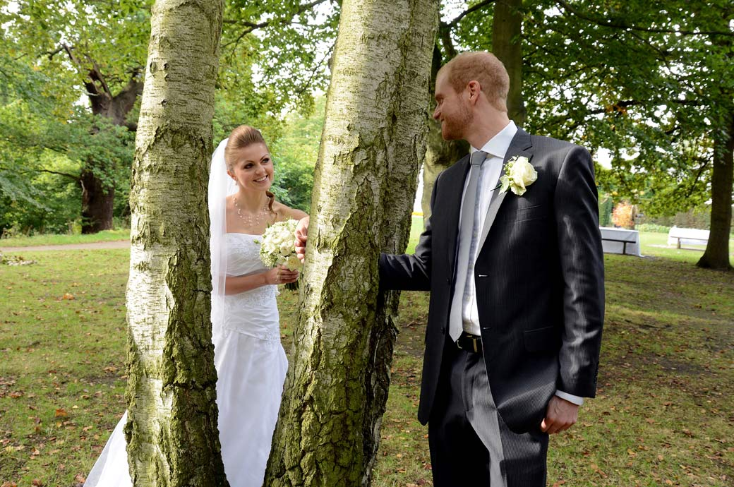 Married couple play and touch hands through the trees in this Pembroke Lodge wedding photo taken below The Russell Suite by Surrey Lane wedding photography
