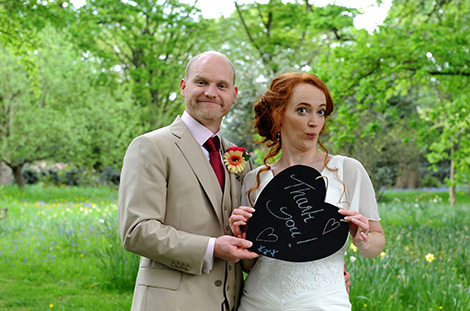 Humorous wedding photo of a Bride and groom having fun posing with their Thank you chalk board at the lovely Surrey wedding venue Pembroke Lodge set in Richmond Park