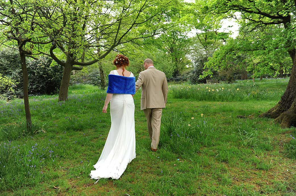 Bride leaves Pembroke Lodge wearing a blue fur stole and follows her Groom into the long grass passing blue bells and daffodils into the beautiful green of Richmond Park Surrey