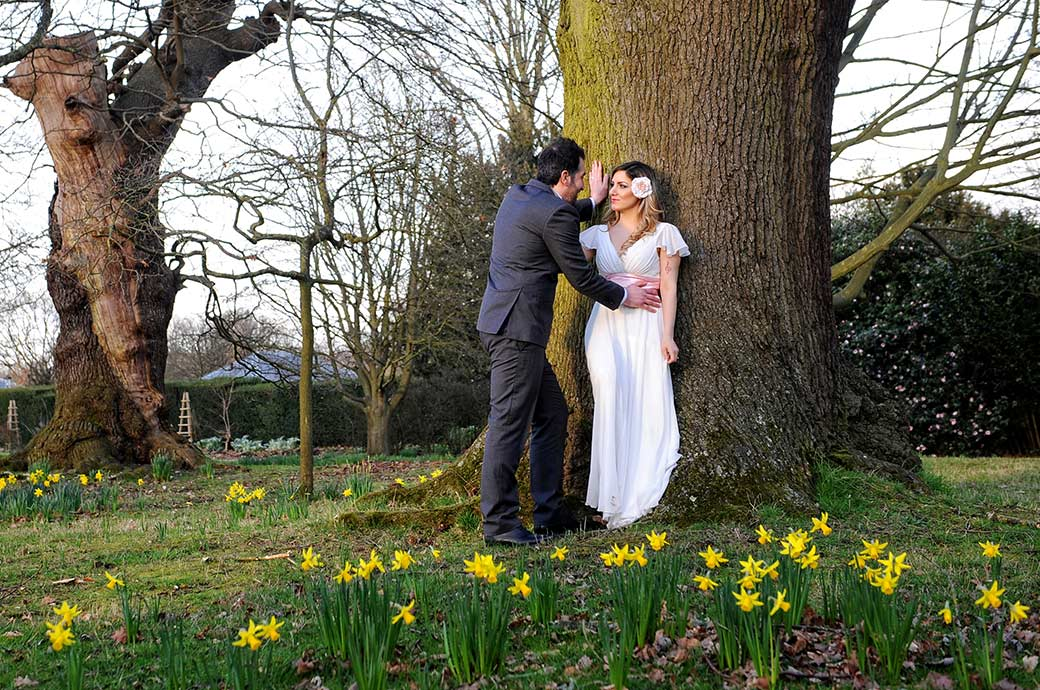 Tender moment for the newlyweds up by an oak tree and beyond the daffodils in the scenic Richmond Park at Surrey wedding venue Pembroke Lodge