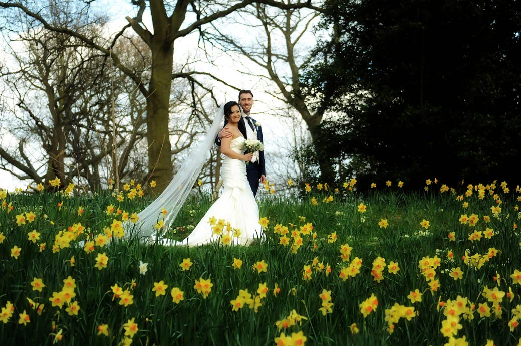 Smiling Bride and Groom as they romantically walk along a path through the bright yellow daffodils in Richmond Park at Surrey wedding venue Pembroke Lodge