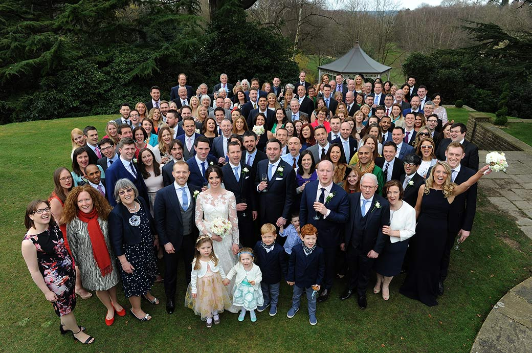 All the guests at the exclusive Surrey wedding venue Pennyhill Park in Bagshot standing on the grass for the popular everyone wedding photo