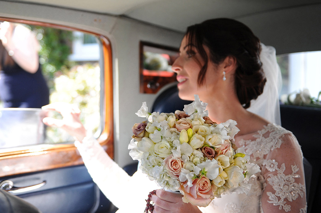 Excited Surrey bride clutches onto her colourful wedding bouquet as she sits in the bridal car on route to the church followed by a Pennyhill Park wedding reception