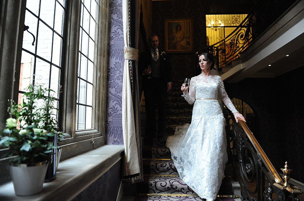 Beautiful elegant Bride at the exclusive and luxurious Surrey wedding venue Pennyhill Park captured as she walks down the stairs with champagne in hand
