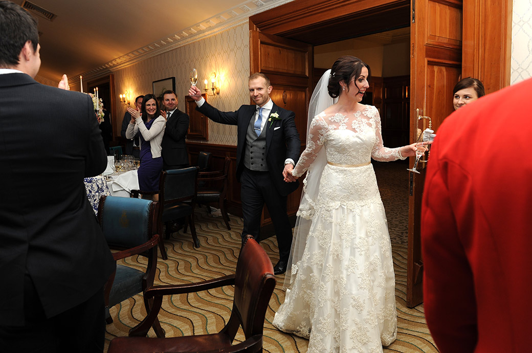 A smiling Bride and groom acknowledge their guests at the Pennyhill Park wedding venue in Surrey as they walk in for their wedding Breakfast in the Balmoral Suite