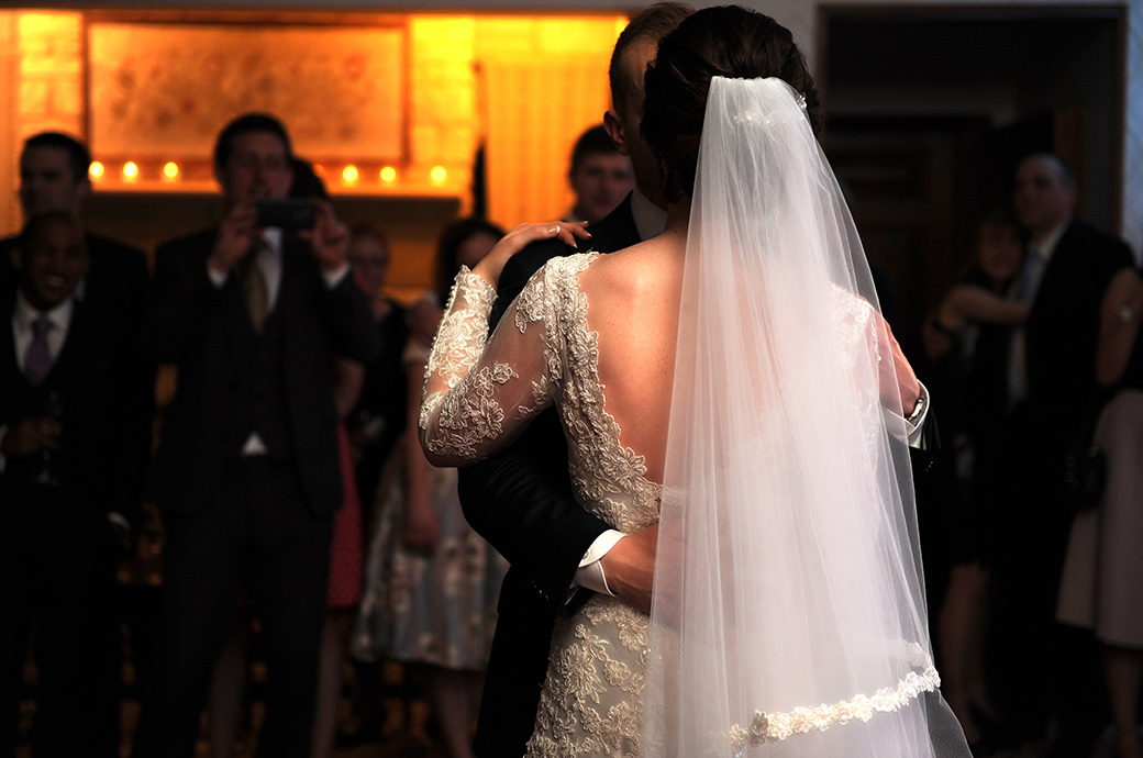 A romantic back shot of the Bride captured during the newlywed's first dance taken in the Sandringham Suite at exclusive Pennyhill Park Surrey wedding venue