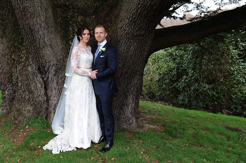 Wedding picture taken at the luxurious Surrey wedding venue Pennyhill Park of a relaxed newlywed couple standing by the large and popular Oak tree on the lower terrace