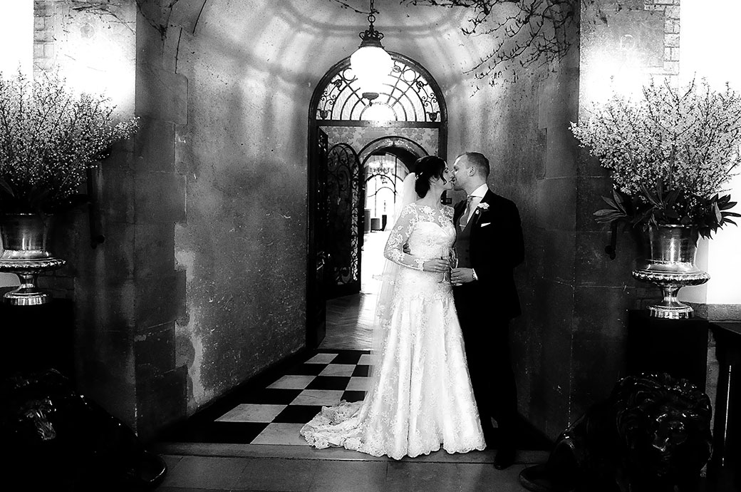 An atmospheric wedding picture of newlyweds at Pennyhill Park Surrey standing with champagne in hand at  the main reception doorway and kissing