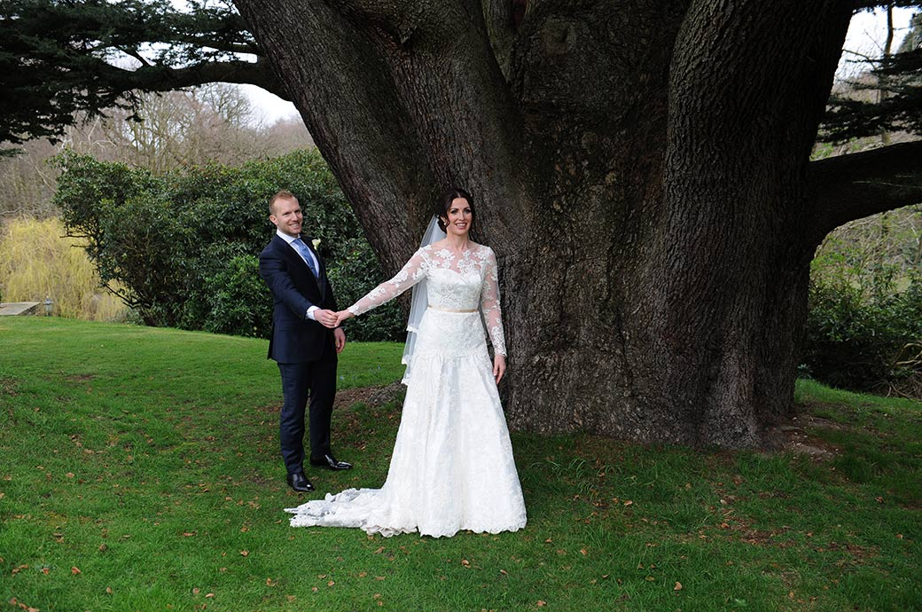 A smiling bride and groom holding hands by the big oak tree on the lower terrace garden at the luxurious Surrey venue Pennyhill Park in Bagshot