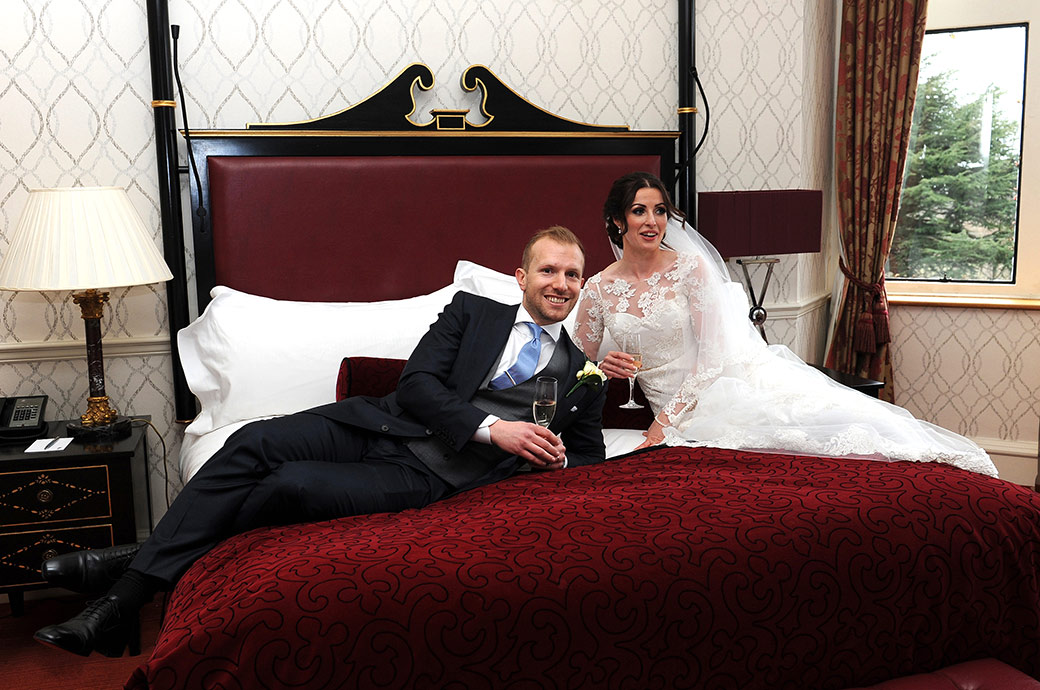 Smiling Groom and Bride relaxing on the bridal bed at the exclusive and luxurious Surrey wedding venue Pennyhill Park with glasses of champagne