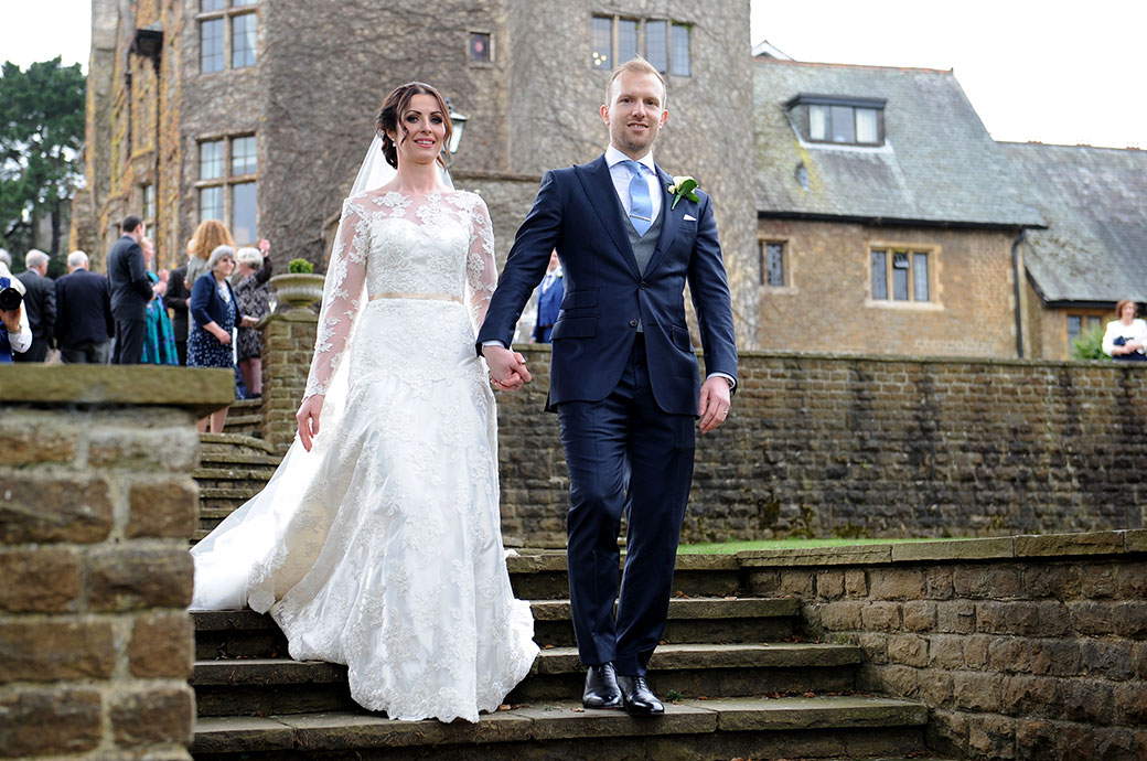 Proud groom at luxurious Surrey wedding venue Pennyhill Park in Bagshot escorts his excited Bride down the stone steps for their romantic walk around the grounds