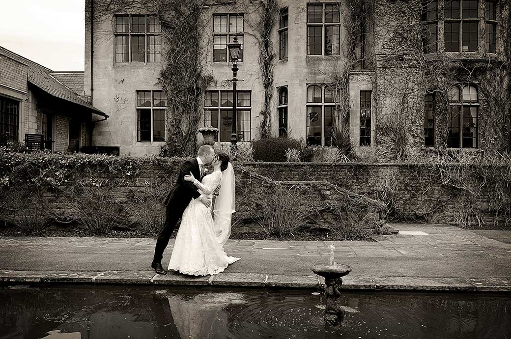 Loving newlyweds at Surrey wedding venue Pennyhill Park captured having a rather dramatic and romantic kiss by the ornamental pond