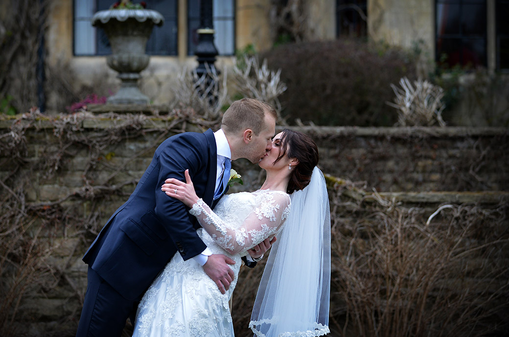 Dramatic and romantic kiss pose by the Bride and groom captured in the garden at the popular Surrey wedding venue Pennyhill Park in the town of Bagshot
