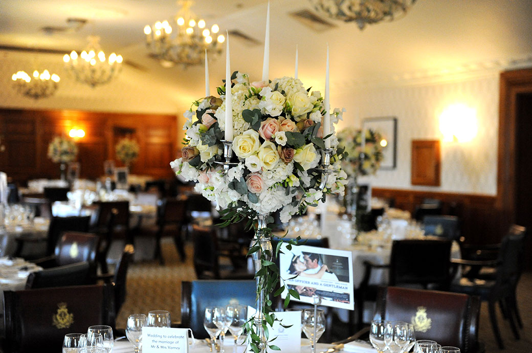 Table candelabra full of beautiful roses ready for the wedding breakfast captured at the luxurious Pennyhill Park venue  in Bagshot Surrey