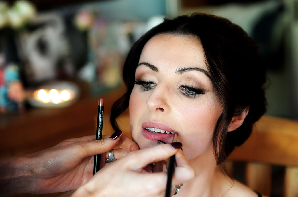 Beautiful Bride captured in the wedding photograph having her lip gloss applied on the morning of her church wedding and Pennyhill Park reception in Surrey