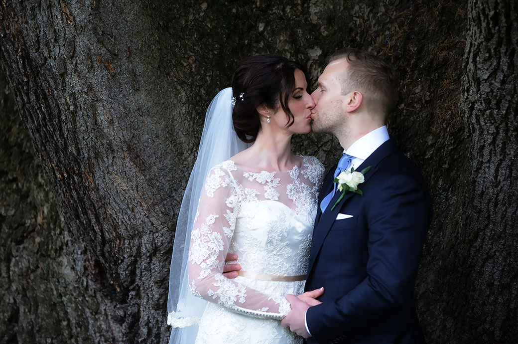 Bride and Groom captured in this romantic wedding photograph taken at the exclusive and luxurious Surrey wedding venue Pennyhill Park as they kiss in front of a large Oak tree