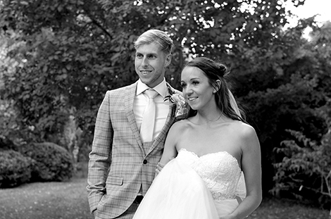 Delightful wedding portrait of an excited Bride and Groom on their walk back to Surrey wedding venue Ramster Hall after a romantic walk around the surrounding grounds