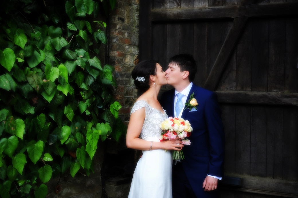 Bride and groom have a passionate kiss as they take some time away from the reception celebrations at the romantic wedding venue Ramster Hall in Surrey