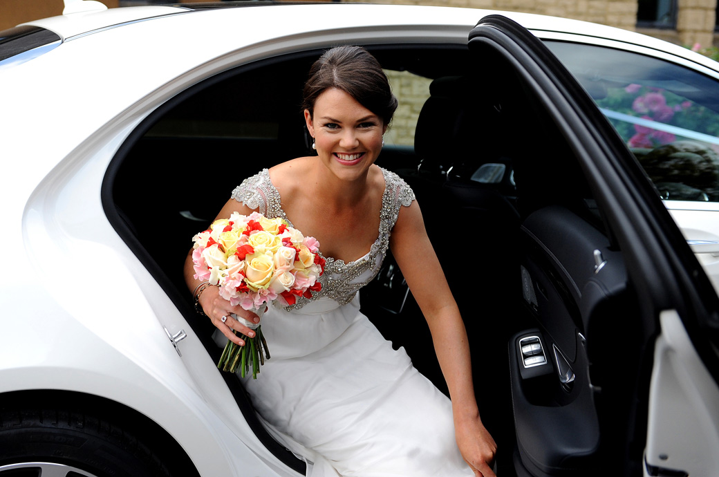 Beautiful happy and smiling Bride clutching her bouquet as she exits the wedding car outside Christ Church New Malden before her reception at Surrey wedding venue Ramster Hall