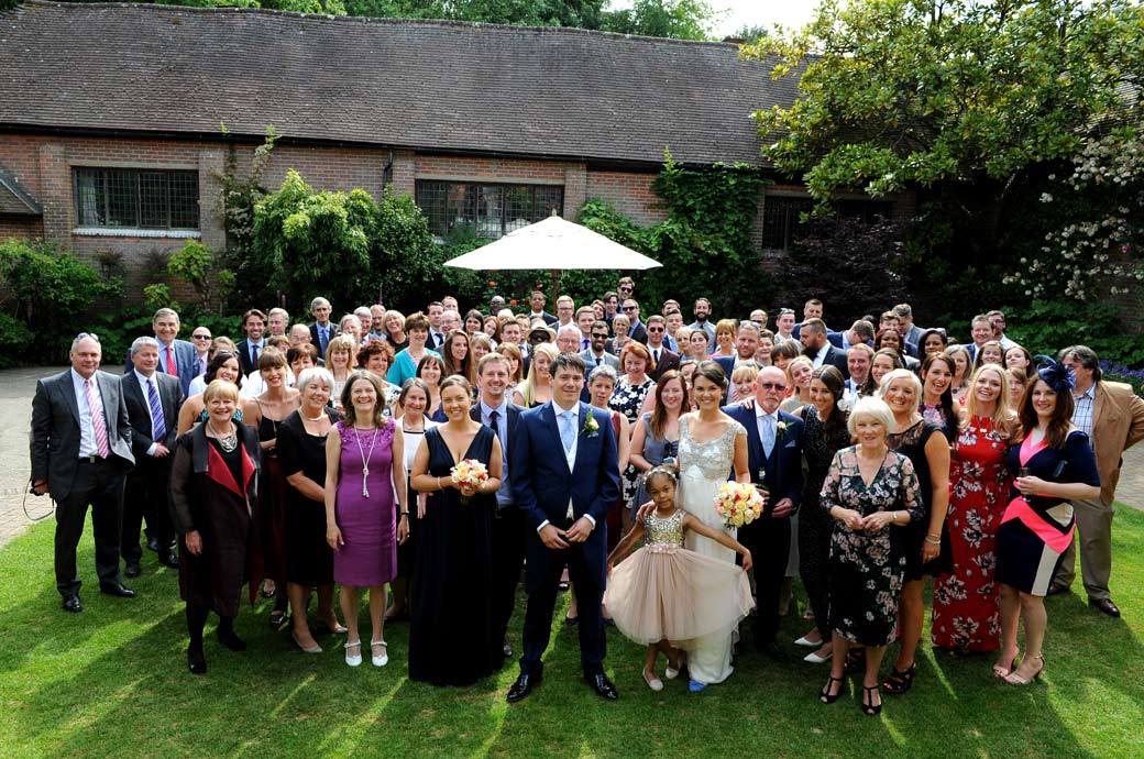 The large and very popular everyone group wedding photo taken in the pretty Courtyard Garden at Ramster Hall in Chiddingfold by a Surrey Lane wedding photographer
