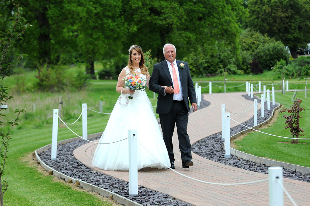 Wedding picture of a lovely smiling bride on her father's arm captured at Surrey wedding venue Reigate Hill Golf Club as they walk to the Waterside venue down the meandering path