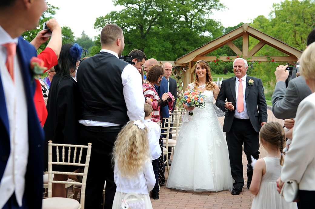 Beaming Bride and Father of the Bride captured at the Waterside wedding venue at Reigate Hill Golf Club Surrey at they get near to the end of the aisle