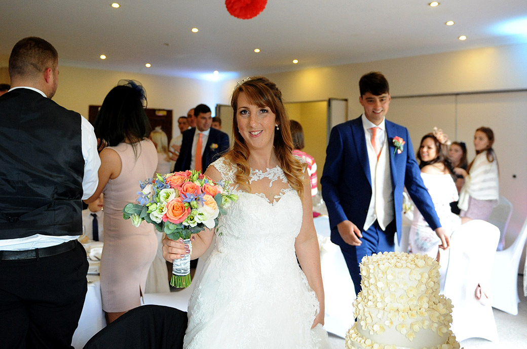 Smiling Bride and groom walk past clapping guests in The Clarence Suite at Reigate Hill Golf Club in Surrey for the start of the wedding breakfast