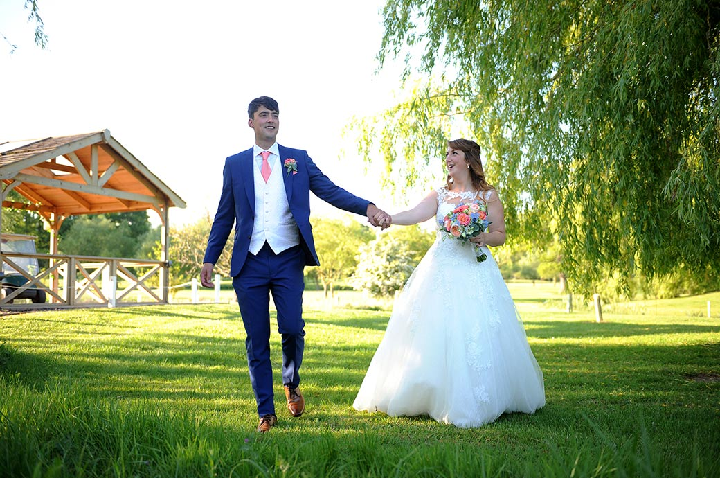 Pure joy captured on the faces of the excited Bride and Groom at Surrey wedding venue Reigate Hill Golf Club as they walk hand in hand across the lawn