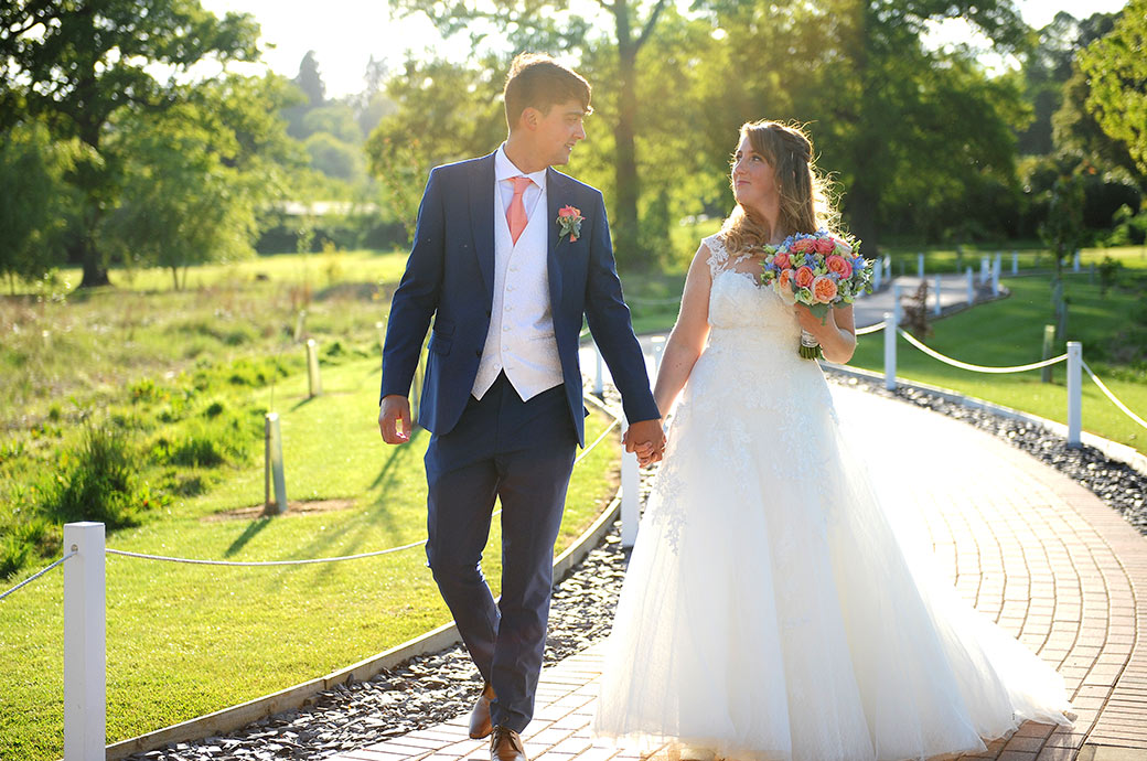 Hand in hand at Surrey wedding venue Reigate Hill Golf Club the excited and happy newlyweds lead the way down the winding path from the outside Waterside venue