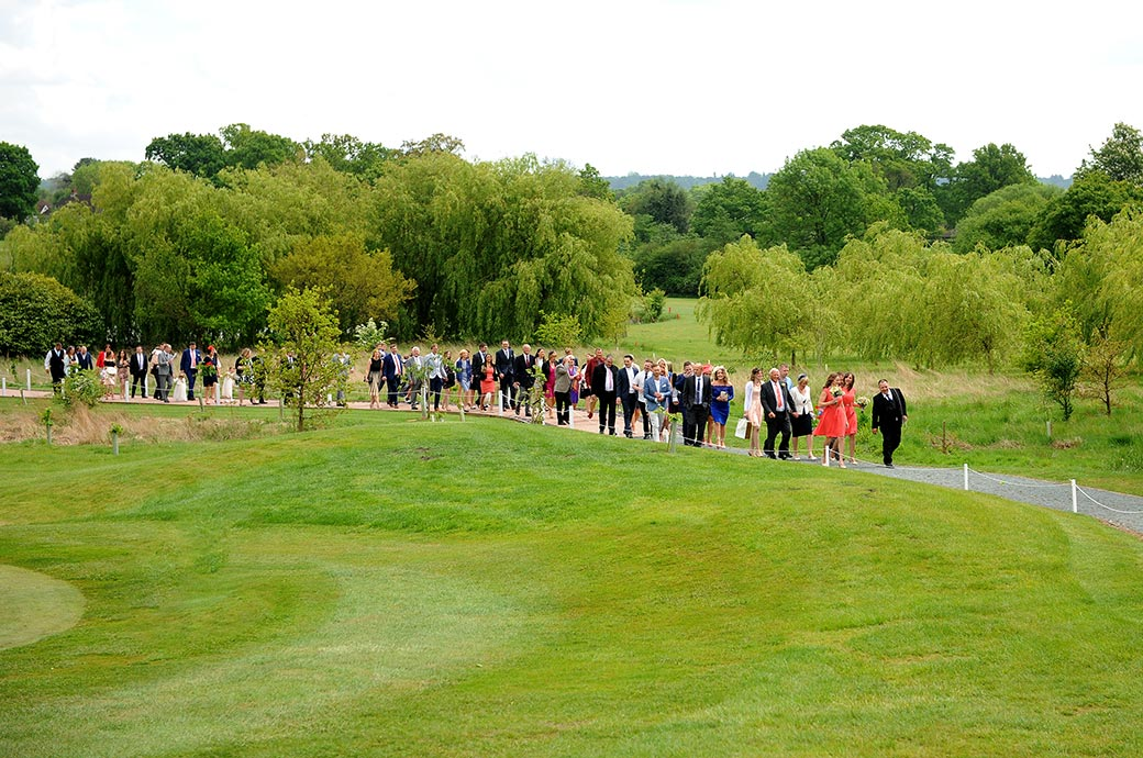 Wedding guests returning to the Reigate Hill Golf Club in Surrey from the outside Waterside venue down the winding path after the marriage ceremony