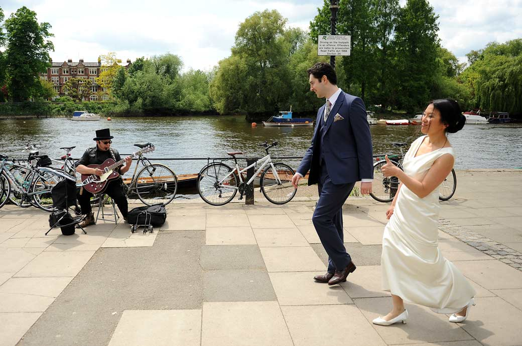 Newly-weds dance past a busker down by The Thames in Richmond Surrey having just got married in  Richmond Register Office