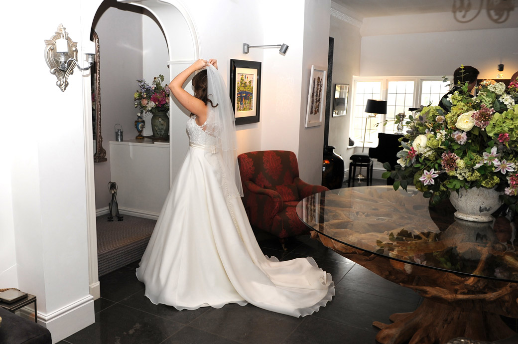 Bride captured in this wedding photo as she makes some adjustments in the welcoming flower filled hall at Surrey wedding venue Russets Country House in the village of Chiddingfold