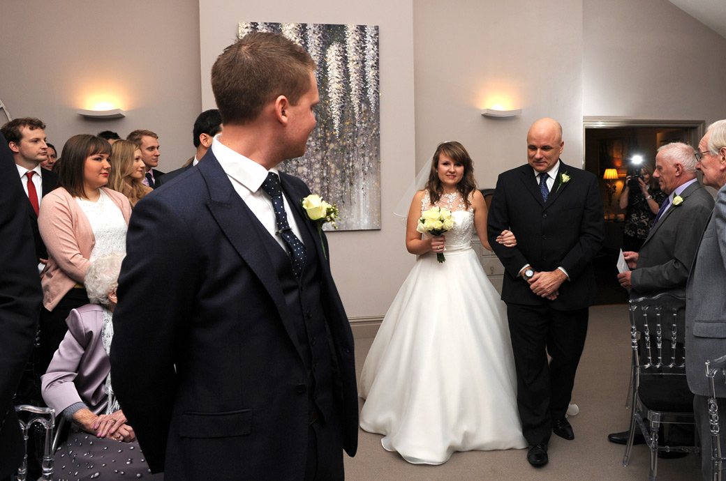 Wedding picture of the Groom's head turned as the Bride walks down the aisle of the Surrey wedding venue  Russets Country House on the arm of her proud father