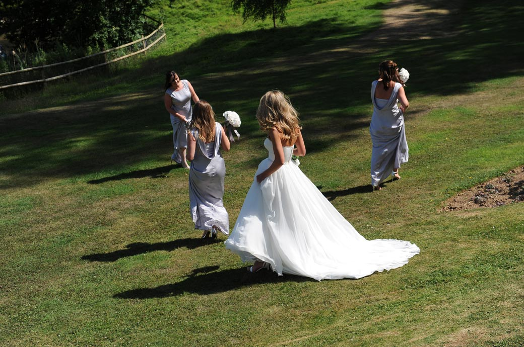 Wedding photo of the Bride following her Bridesmaids down a grass slope in the lovely landscaped gardens at Russets Country House  in Chiddingfold, Godalming Surrey