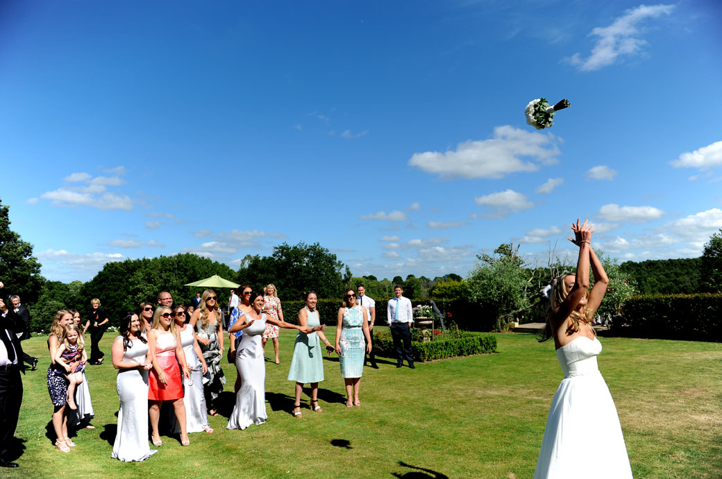 Bride throwing her wedding bouquet high into the air for the awaiting ladies to catch at the wonderful Surrey wedding venue in Chiddingfold Russets Country House