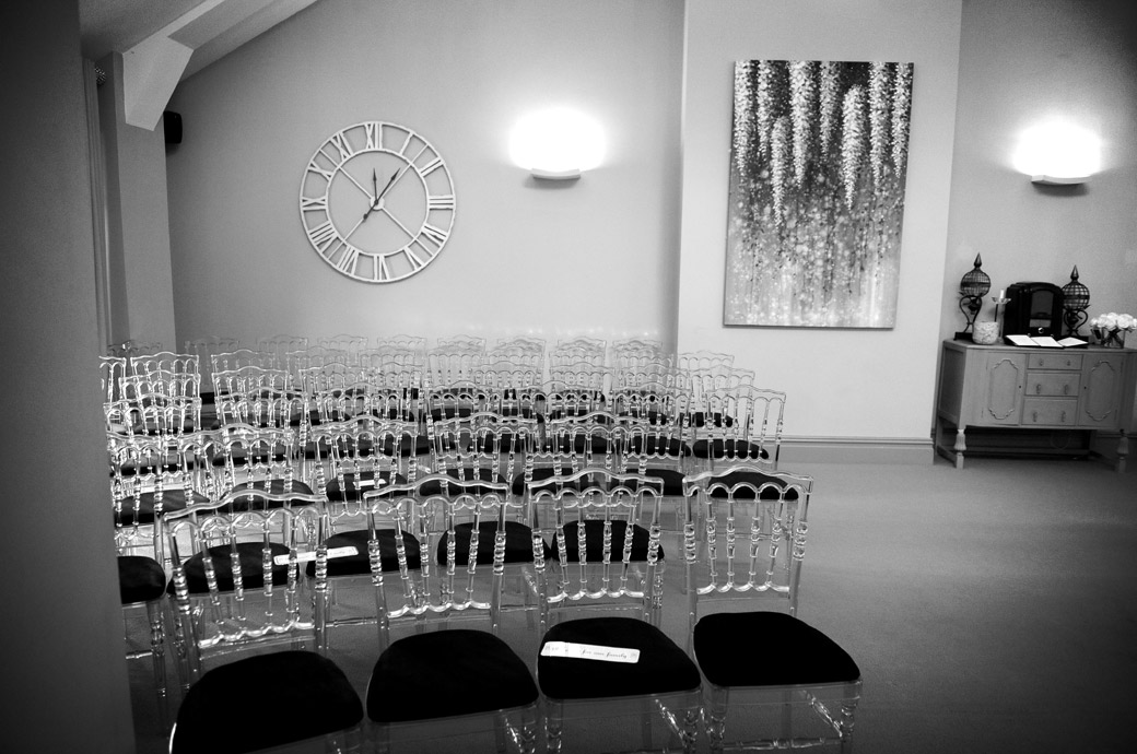 Clock marks the time in this wedding picture taken at Surrey wedding venue Russets Country House Chiddingfold Godalming looking over the glass chairs in the marriage ceremony  room