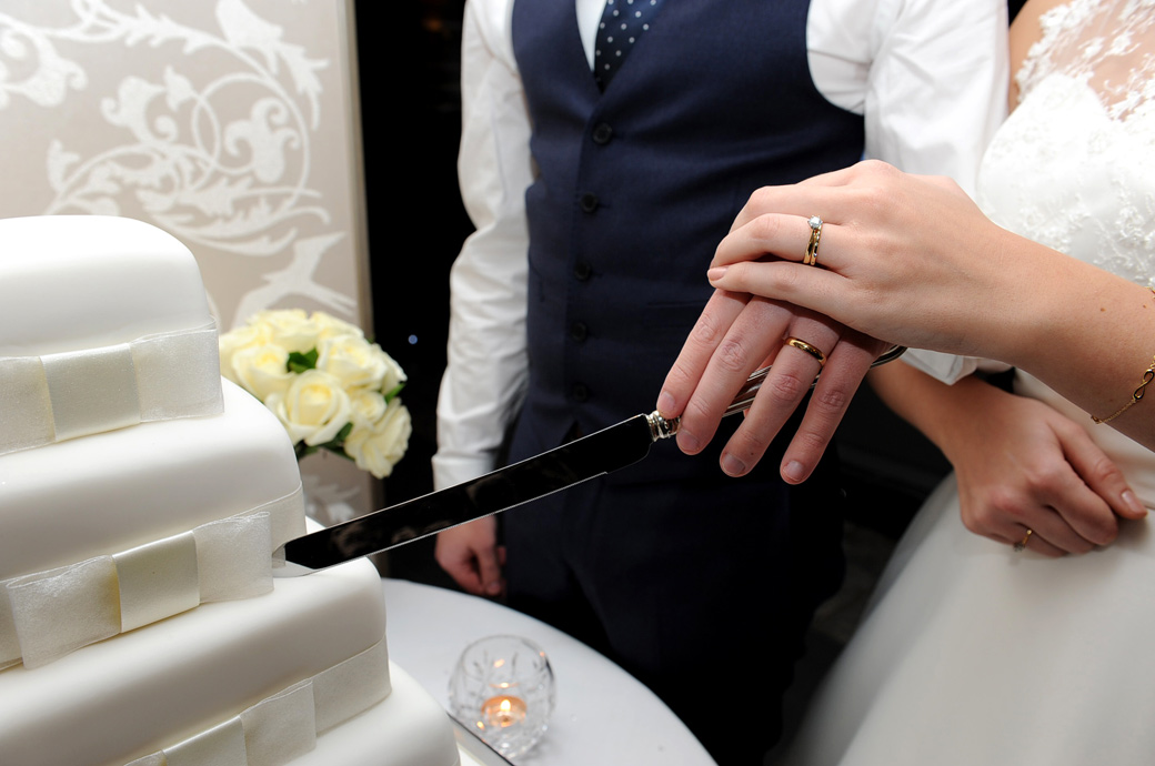 Close up wedding photo of the Bride and Groom's wedding rings taken as they are about to cut the wedding cake at Russets Country House in Chiddingfold in the Surrey countryside