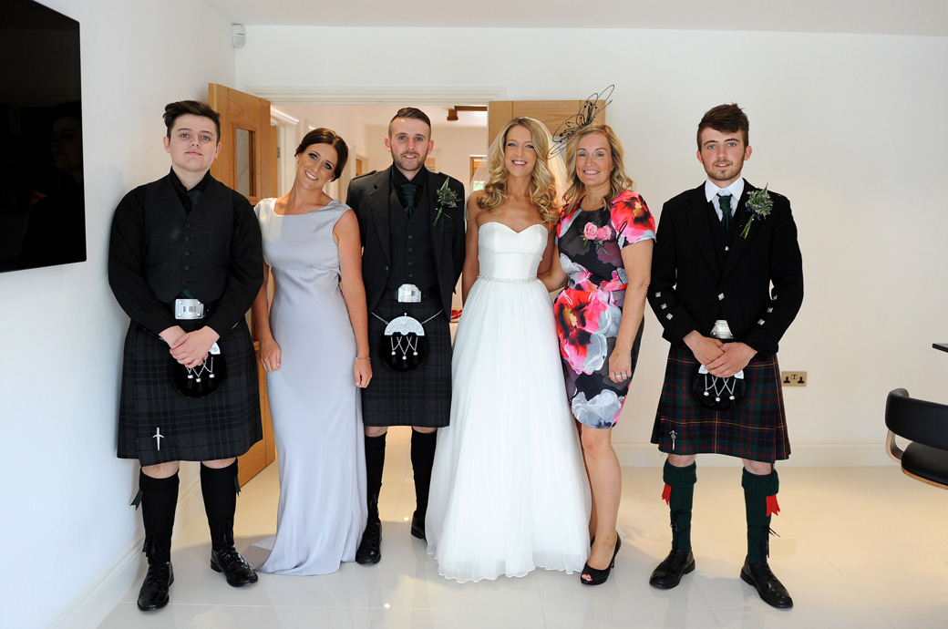Family wedding photograph with lovely dresses and classic kilts taken before the church wedding and reception at Russets Country House a Surrey wedding venue in Chiddingfold village