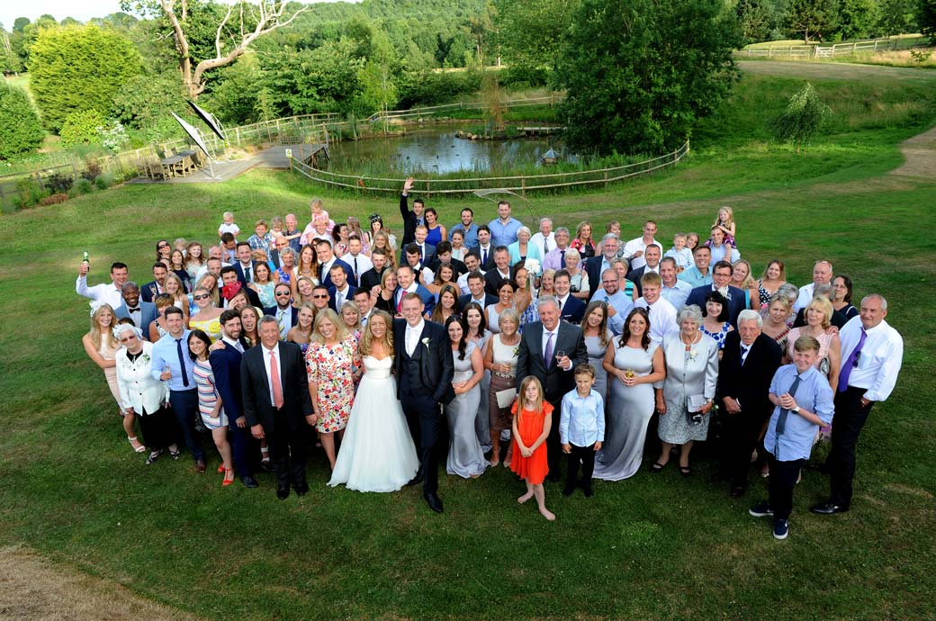 An everyone group wedding photograph taken from the terrace at Surrey wedding venue Russets Country House with the picturesque pond in the background