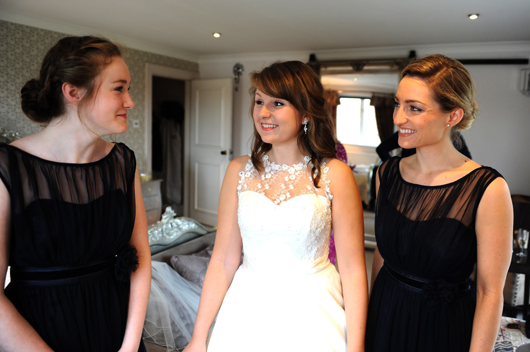 Excited Bride in this wedding picture taken in the bridal suite at Russets Country House in Chiddingfold Surrey as she shares a moment of fun with her lovely Bridesmaids