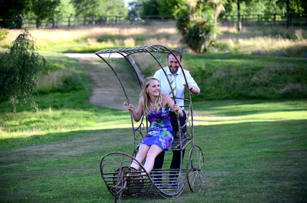 Wedding guests having fun on an interesting looking ornamental wrought iron garden chair in the gardens at Russets Country House by a Surrey Lane wedding photographer