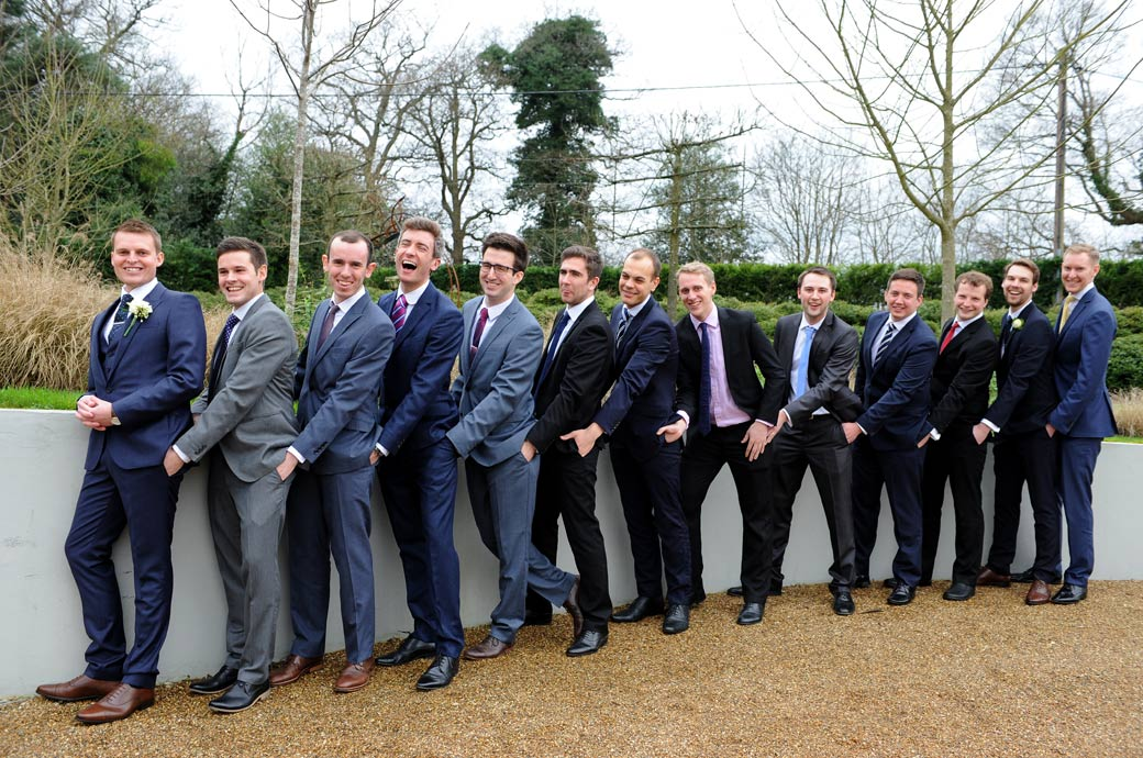 Groom and gents have fun in this hilarious wedding photograph taken outside Russets Country House in Surrey of them all putting their hands in another's trouser pockets