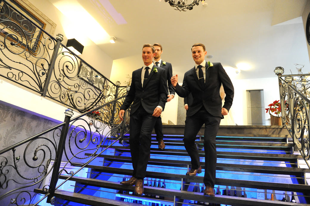 Happy looking groomsmen captured in this wedding photo as they descend the stairs to join the wedding reception at the stunning Surrey venue Russets Country House